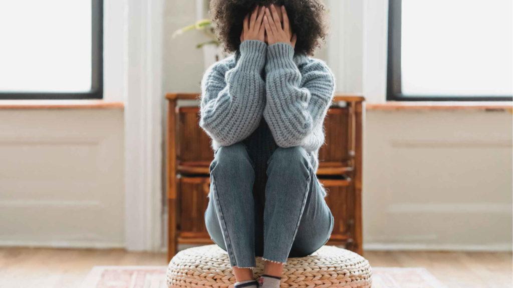 Девушка сидит на полу и закрывает лицо руками