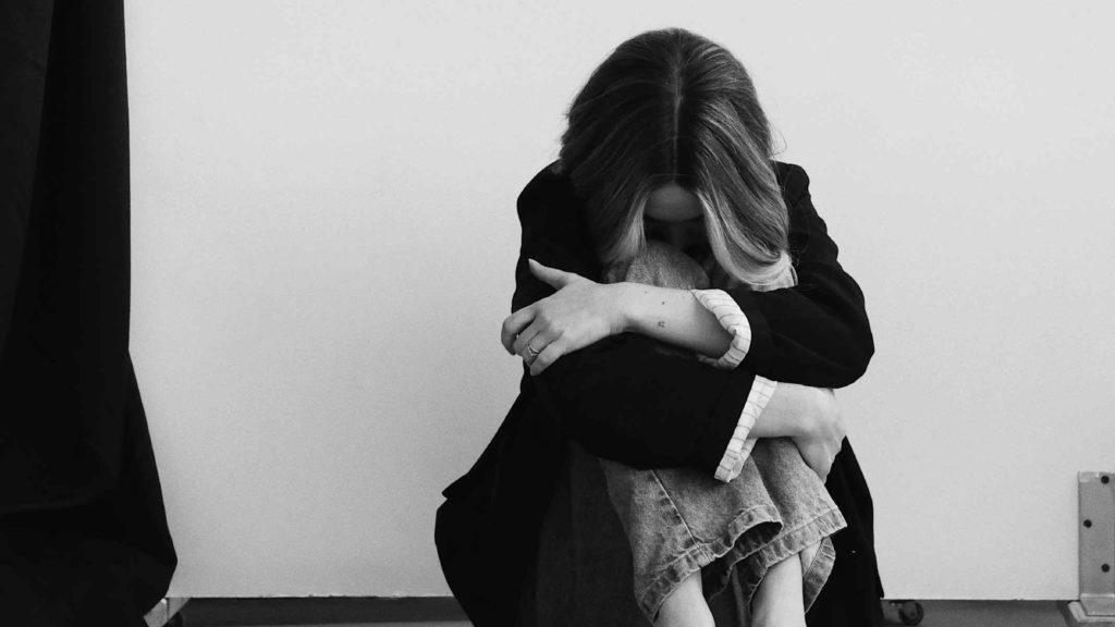 Девушка сидит на полу обнимает себя и грустит