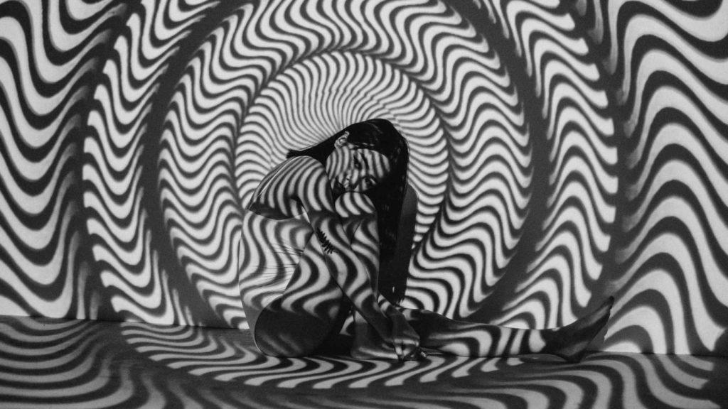 Девушка сидит с отражением на стене узора гипноза