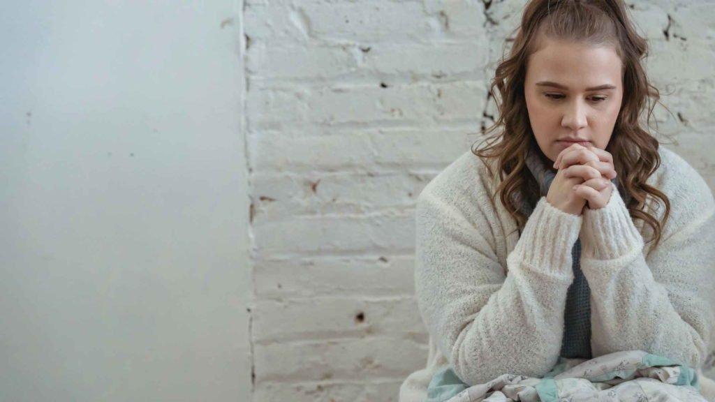 Девушка сидит у белой стены и думает