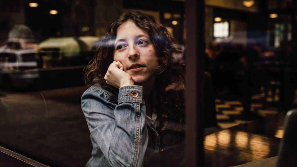 Девушка сидит в кафе и задумчиво смотрит на улицу