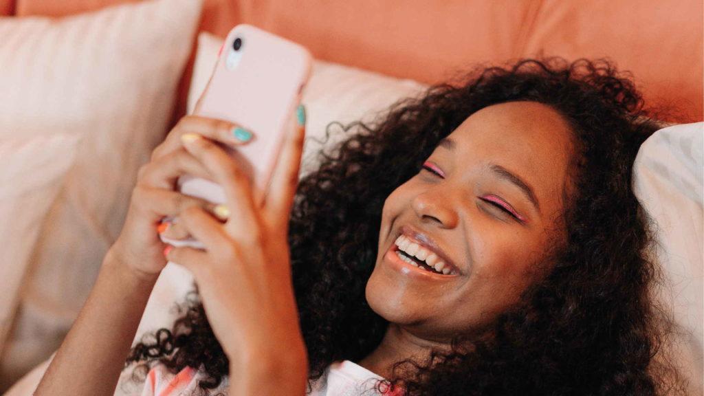 Девушка смеется глядя в телефон