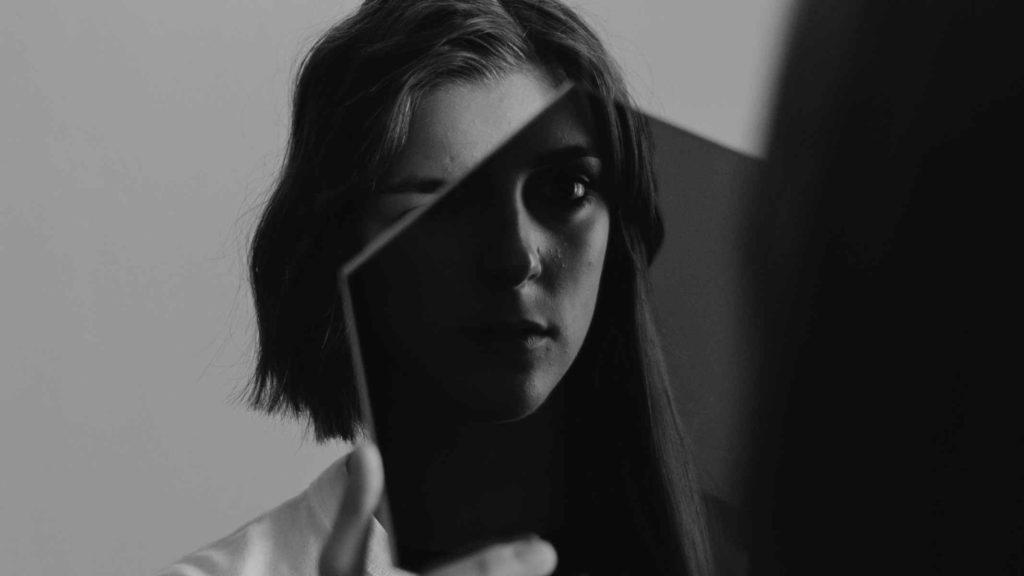 Девушка смотрит на свое отражение в маленькое зеркало