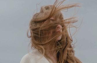 Девушка стоит на улице и ветер растрепал ей волосы