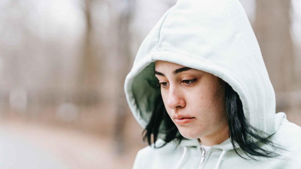 Девушка в капюшоне от худи грустит