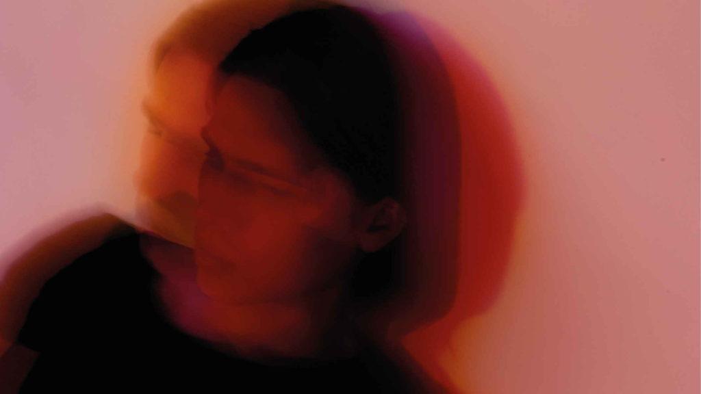 Девушка в красном освещении с эффектом размазанным
