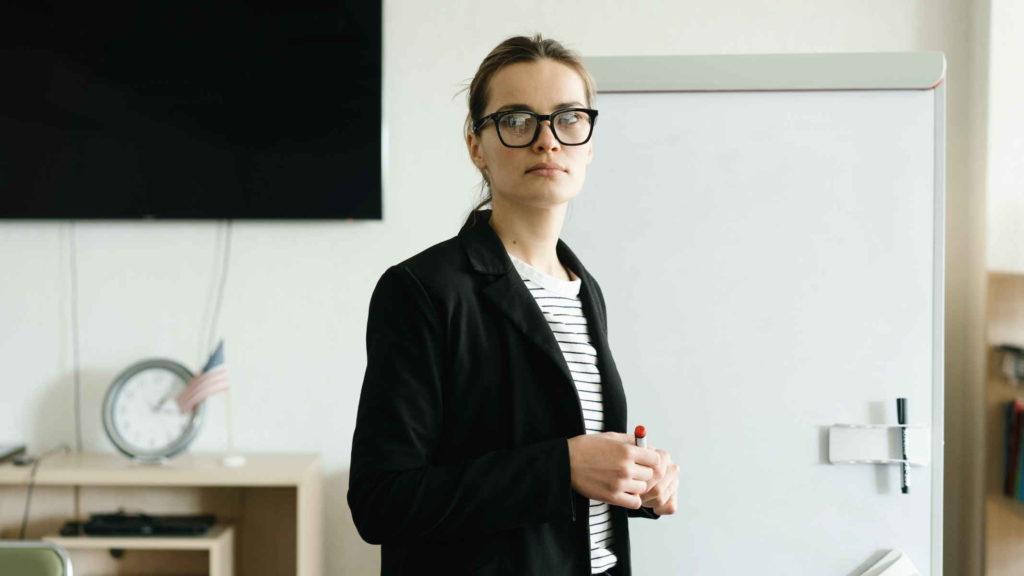 Девушка в очках и костюме стоит в кабинете