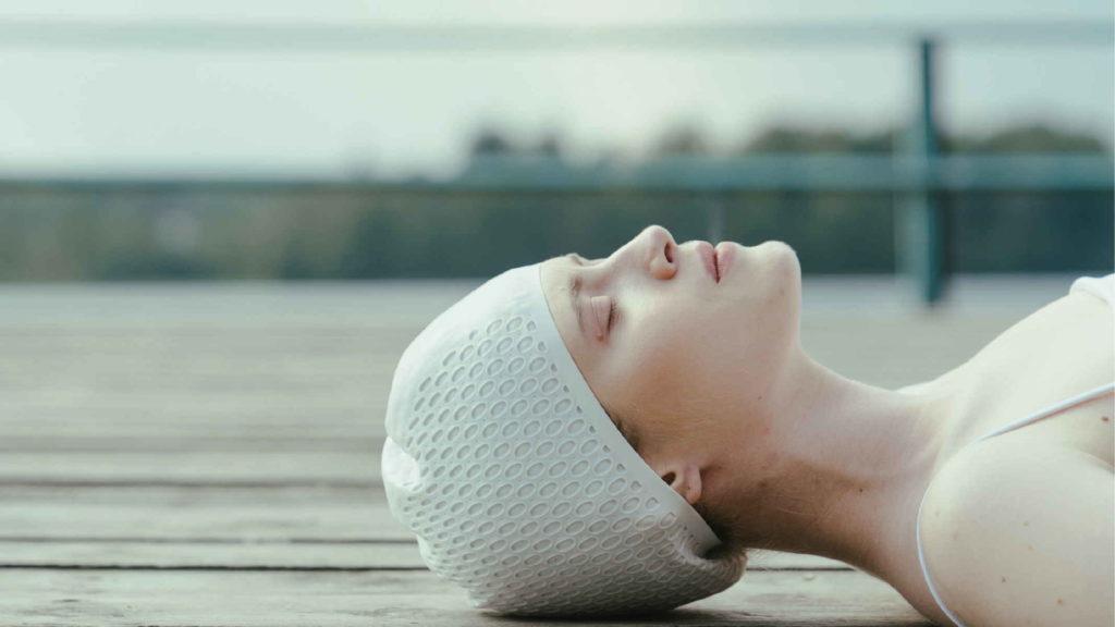 Девушка в шапочке для плавания лежит на мостике и рефлексирует