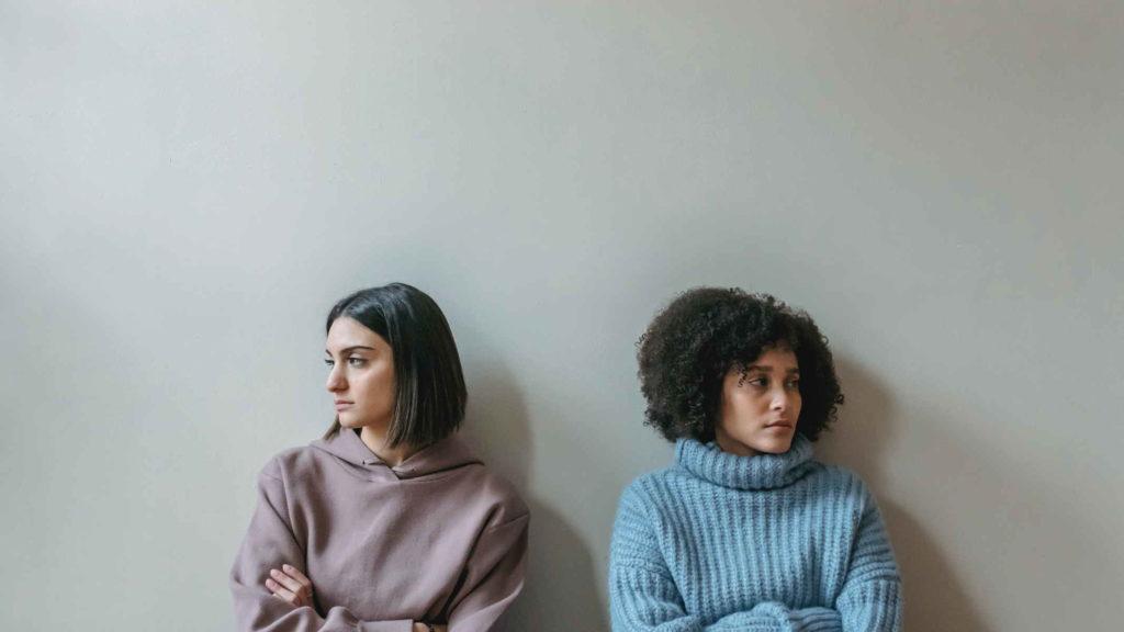 Две девушки отвернулись друг от друга сидя у стены