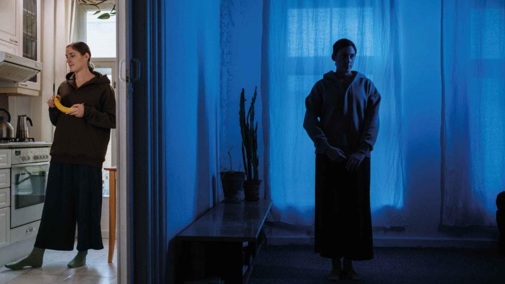 Две девушки стоят в разных комнатах при разном освещении