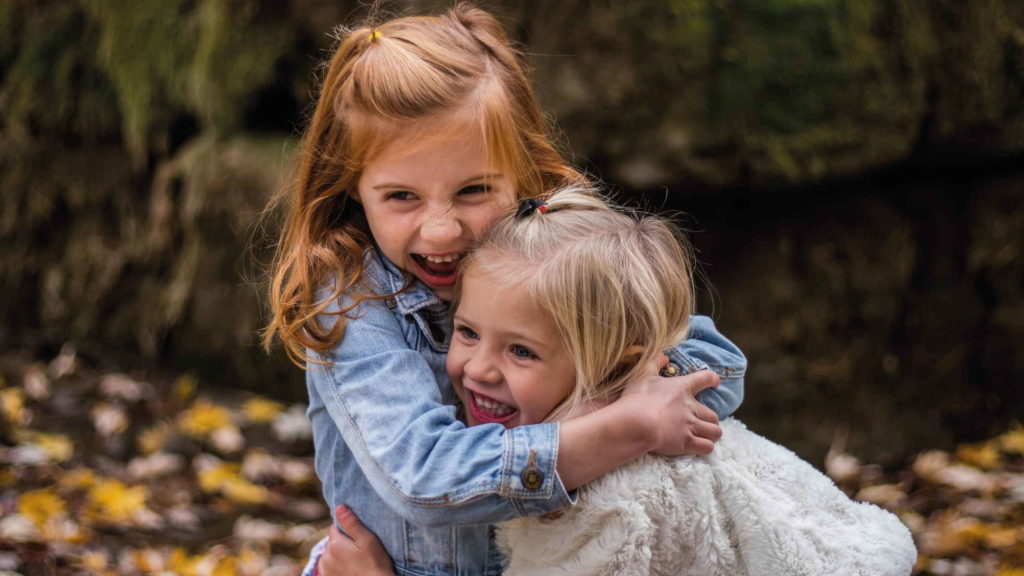 Две маленьких светловолосых девочки обнимаются