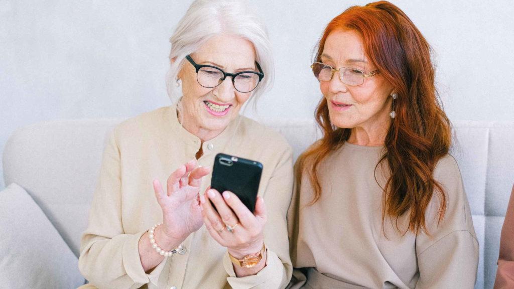 Две пожилые женщины смотрят в телефон и улыбаются