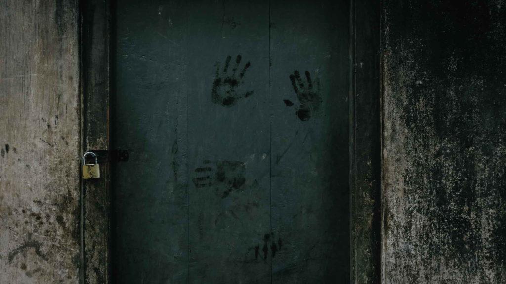 Дверь старого дома с отпечатками человеческих рук