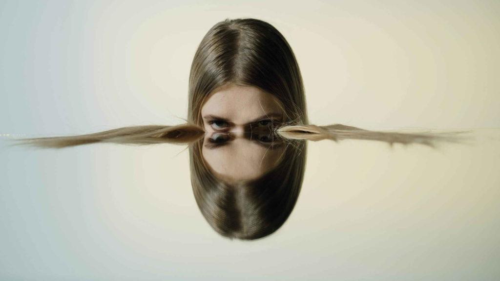 Голова девушки отражается в зеркале наполовину