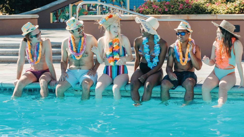 Группа друзей сидит в бассейне и разговариват