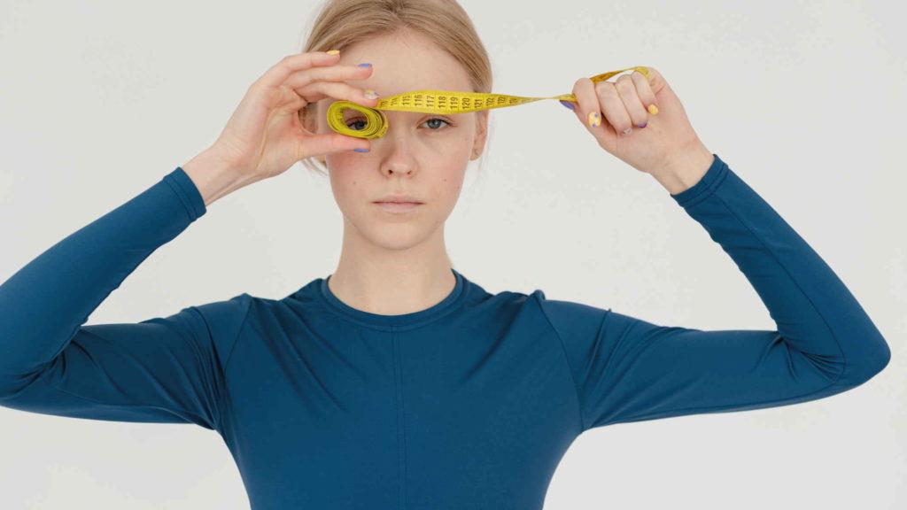 Худая девушка в синей кофте держит метр