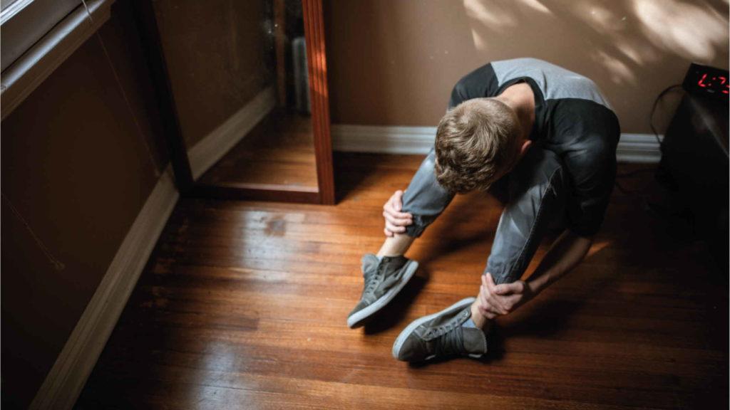 Мальчик сидит на полу и страдает
