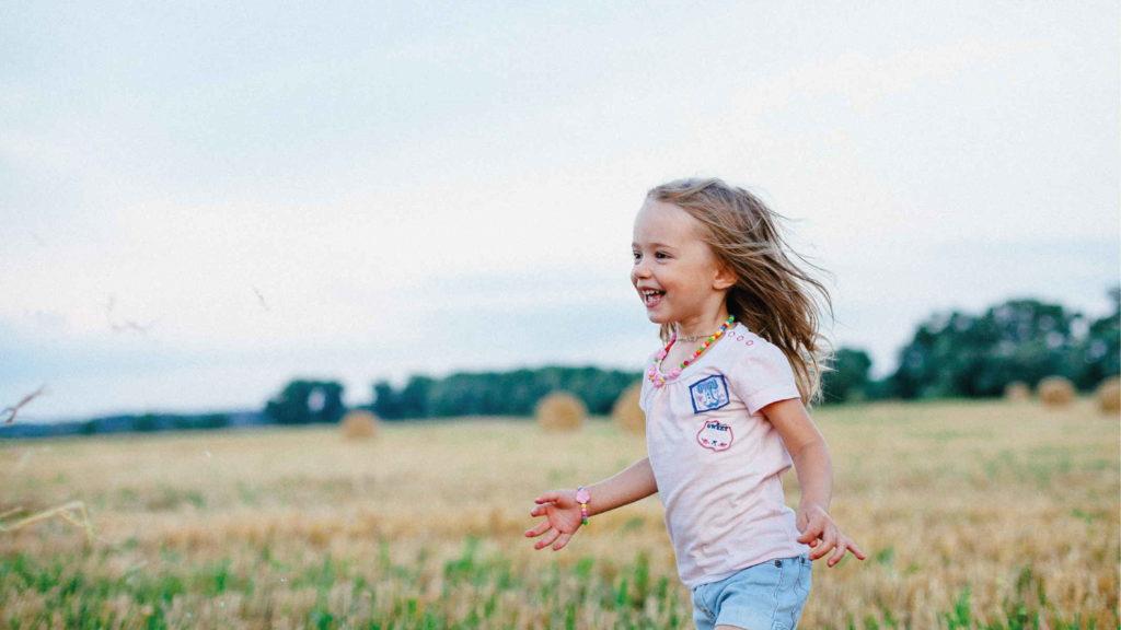 Маленькая девочка бежит по полю