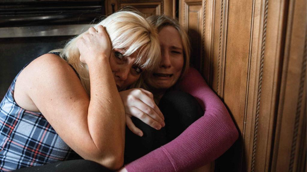 Мать и дочь скрываются в углу от угрозы