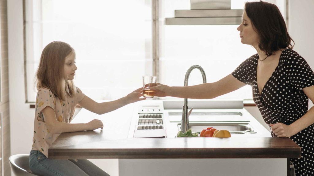 Мать передает дочери стакан с водой