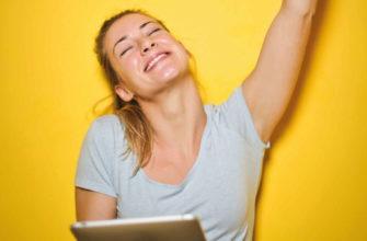 Молодая девушка радуется на фоне яркой желтой стены