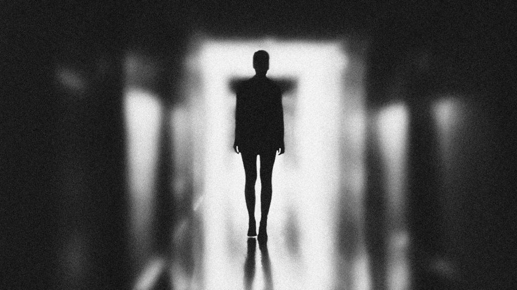 Монохромное изоражение женщины идущей по коридору