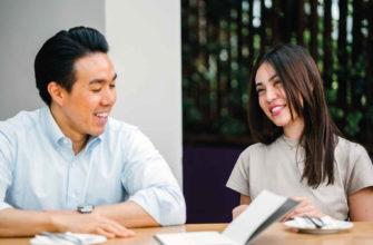 Мужчина и девушка общаются за столиком на улице