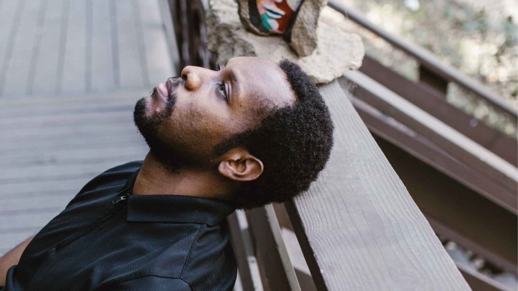 Мужчина на улице расслаблено сидит и смотрит вверх
