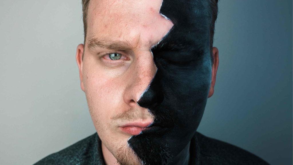 Мужчина раскрасил половину лица в черный цвет