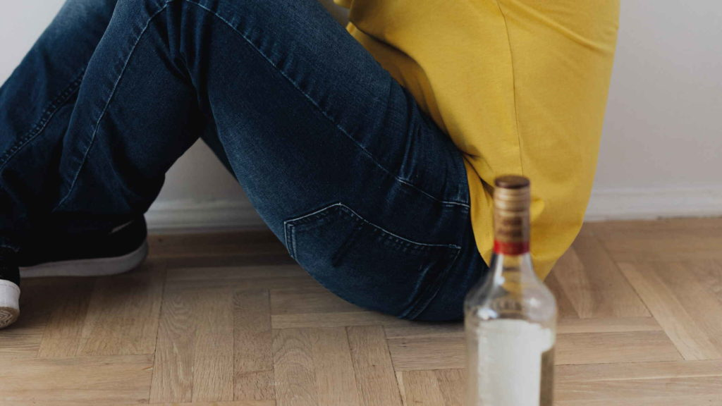 Мужчина сидит на полу рядом с бутылкой алкоголя