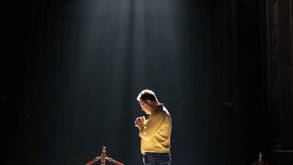 Мужчина стоит в храме и молится