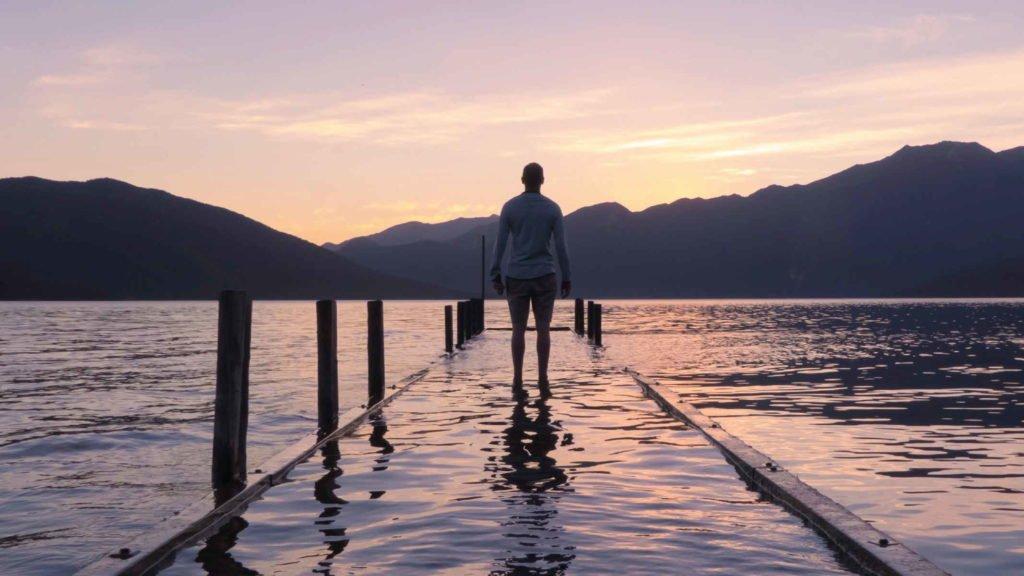 Мужчина стоит в воде на фоне гор и заката