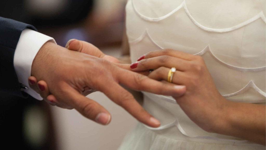 Невеста надевает обручльное кольцо жениху на палец