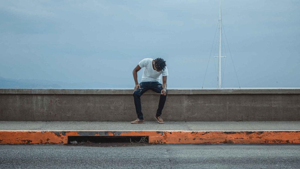 Одинокий парень сидит на мосту