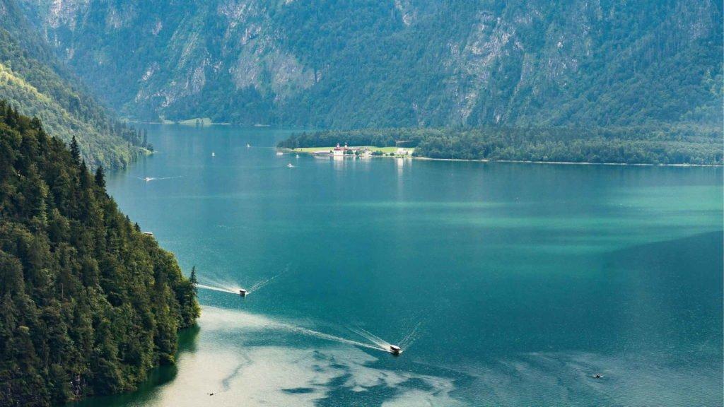 Пейзаж гор и озера по которому плывут катеры