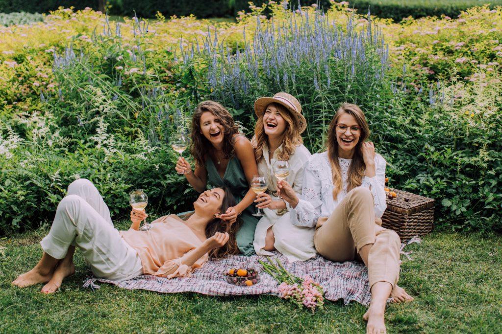 Подруги сидят на пикнике и смеются