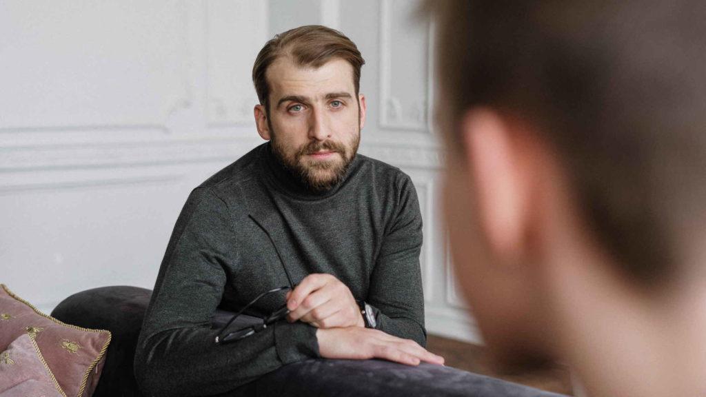Психолог облокотился на диван и смотрит с добром на клиента