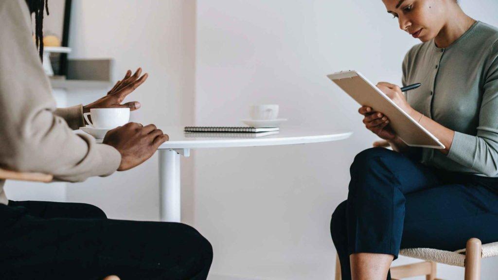 Психолог записывает слова своего клиента мужчины