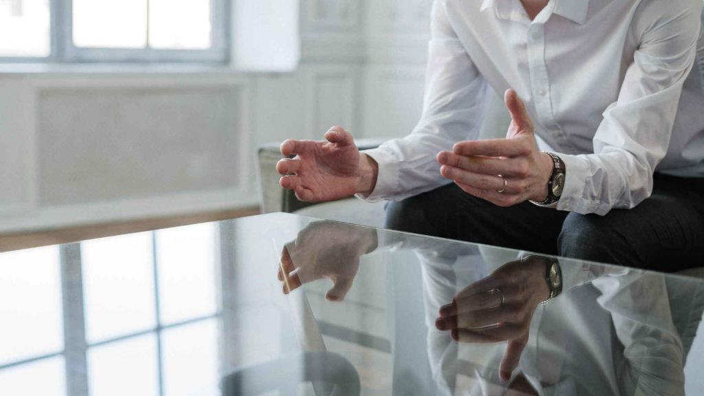 Руки мужчины в белой рубашке отражаются в стеклянном столе