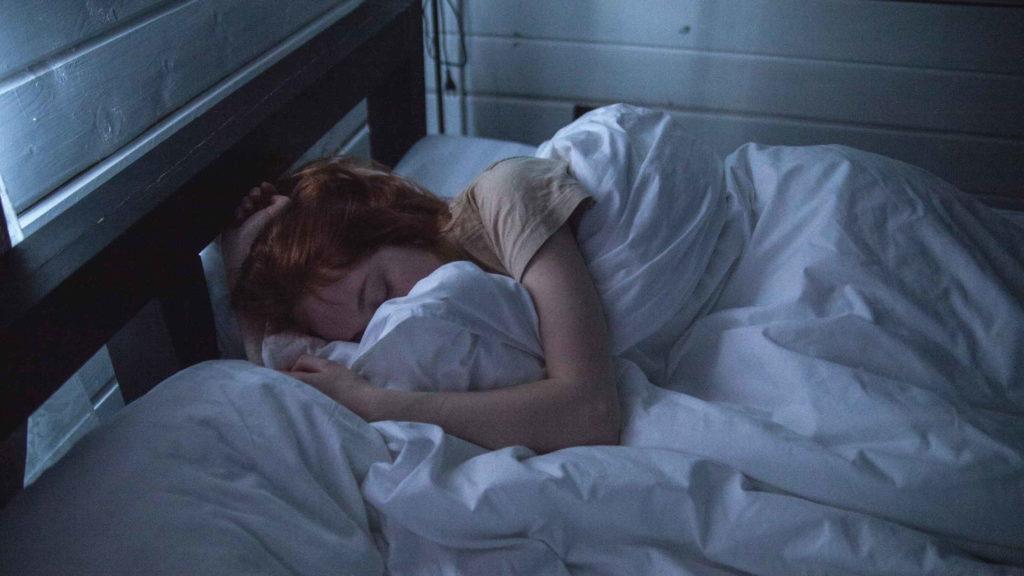 Рыжеволосая девушка спит в кровати