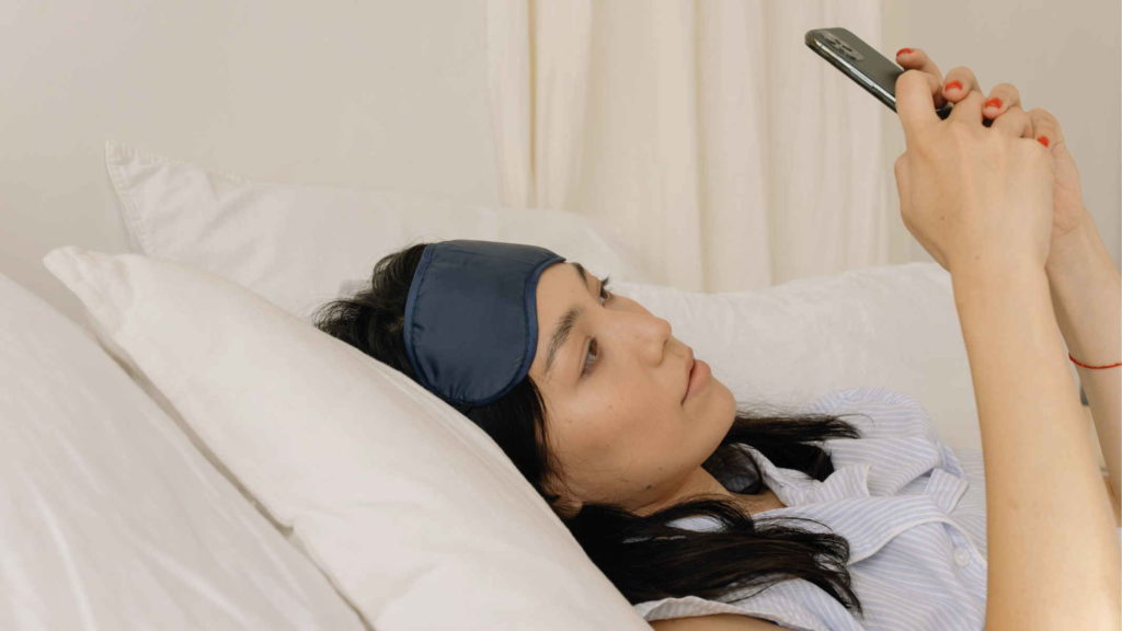 Сонная девушка лежитв. кровати и смотрит в телефон