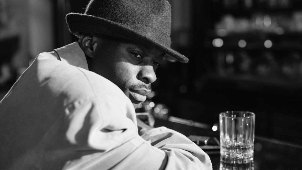 Темнокожий мужчина в шляпе и плаще сидит в баре
