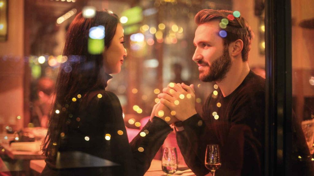 Влюбленная пара смотрит друг к другу в глаза в кафе и держится за руки