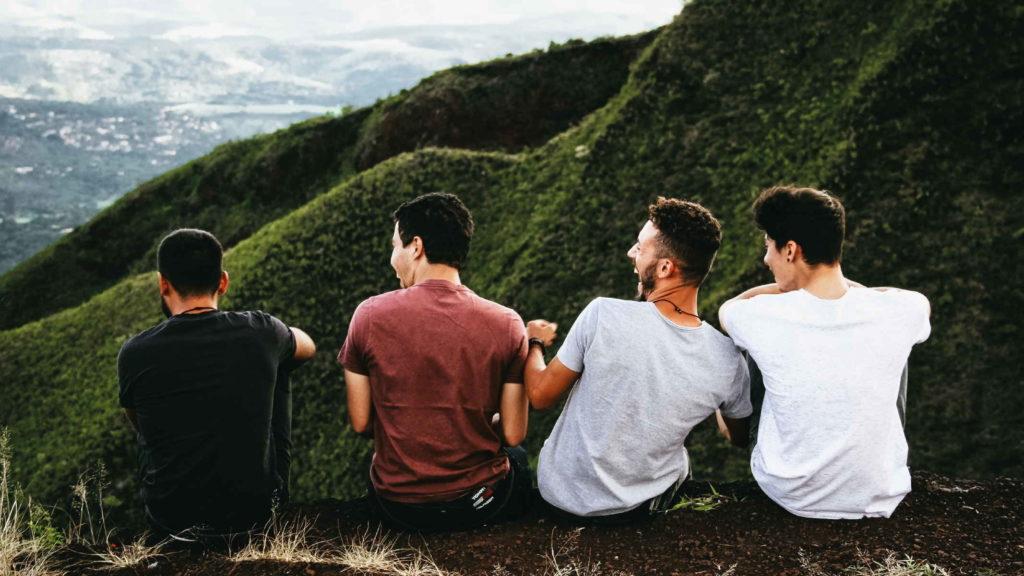 Четверо мужчин сидят на горе