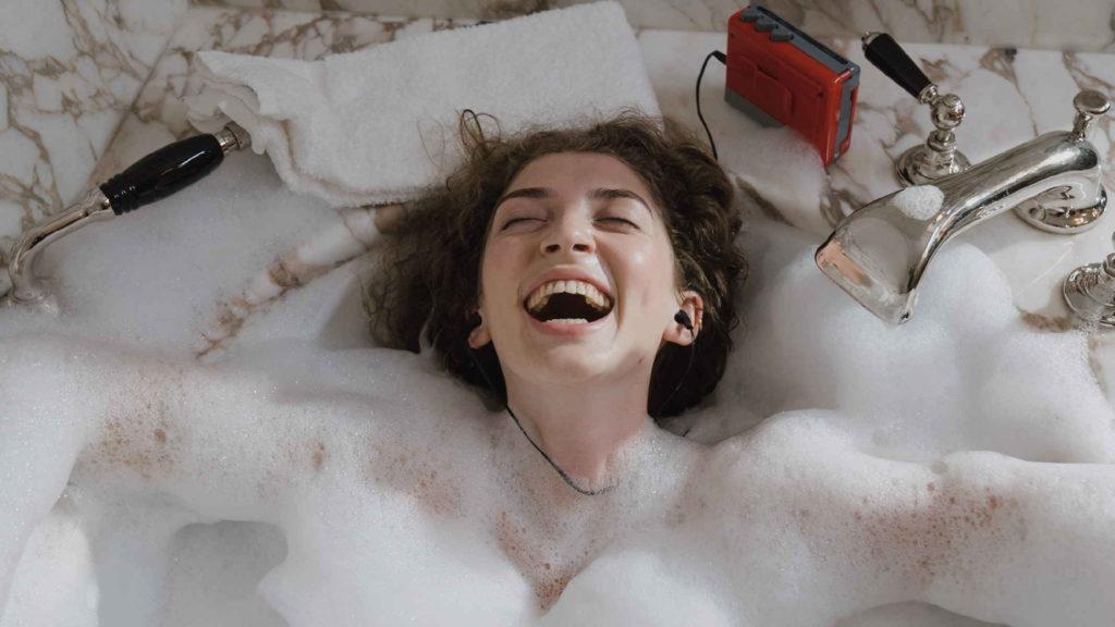 Девушка лежит в ванне с пеной