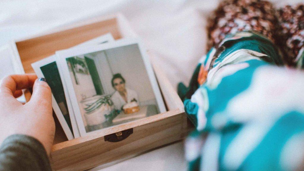 Девушка перебирает коробочку с фотографиями