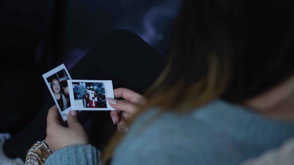 Девушка рассматривает фотографии с полароида