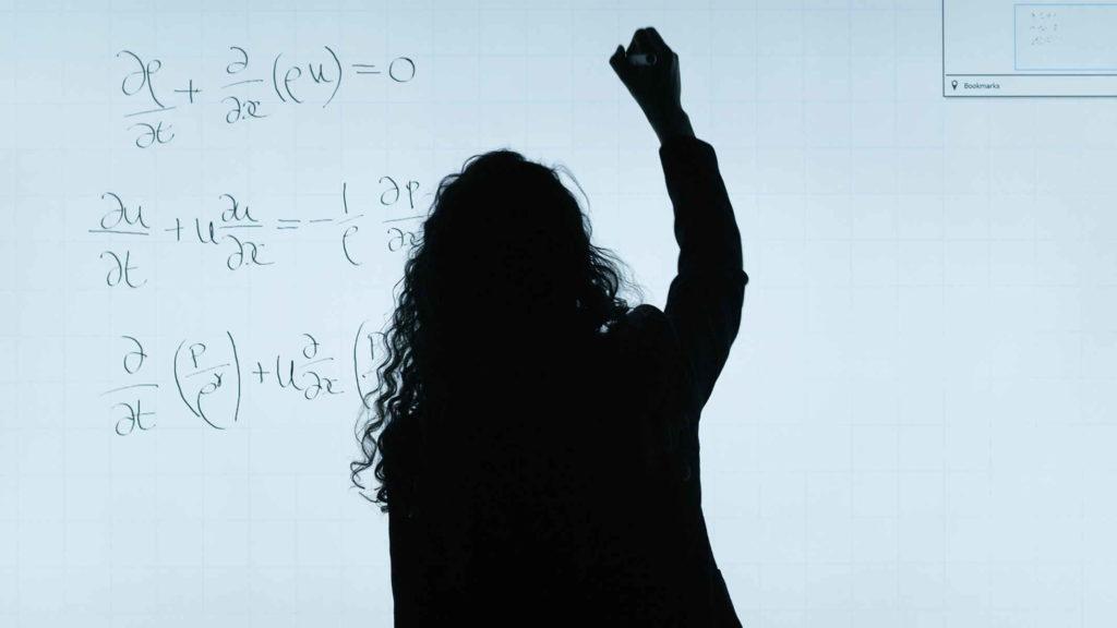 Девушка ученая пишет формулу вычислений на доске