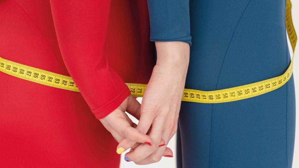 Две девушки измеряют пропорции и держатся за руки
