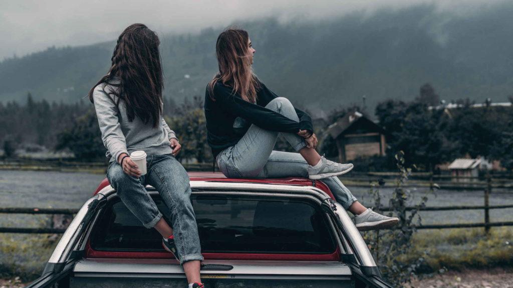 Две девушки сидят на крыше автомобиля и смотрят на небо